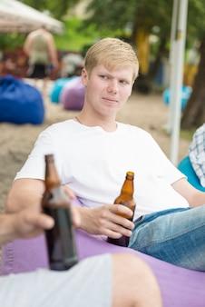 Homme avec de la bière relaxant entre amis