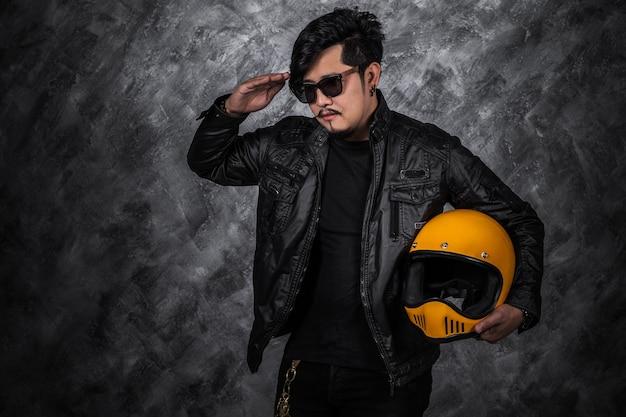 Homme biker en blouson de cuir noir saluant et tenant un casque