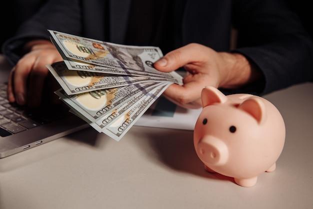 Homme avec des billets en dollars dans sa main travaillant à l'aide d'un ordinateur portable