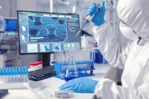 Homme biochimiste prenant un échantillon de liquide tenant une pipette automatique. chimiste dans un laboratoire moderne faisant des recherches à l'aide d'un distributeur pendant l'épidémie mondiale avec covid-19.