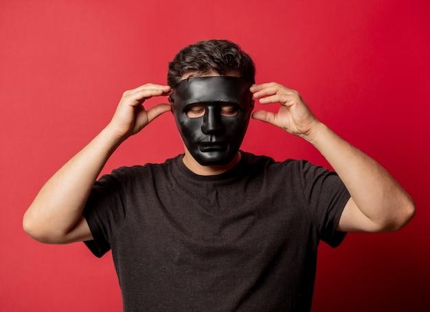 Homme blanc au masque noir sur l'espace rouge