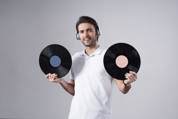 Homme blanc posant avec des disques vinyles isolés.