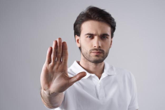 Homme blanc posant avec le geste de la main isolé.