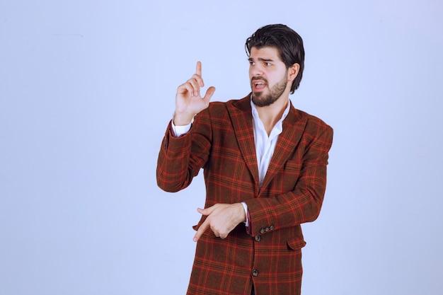 Homme en blazer à carreaux ayant un discours dans la scène et présentant quelque chose ci-dessus.