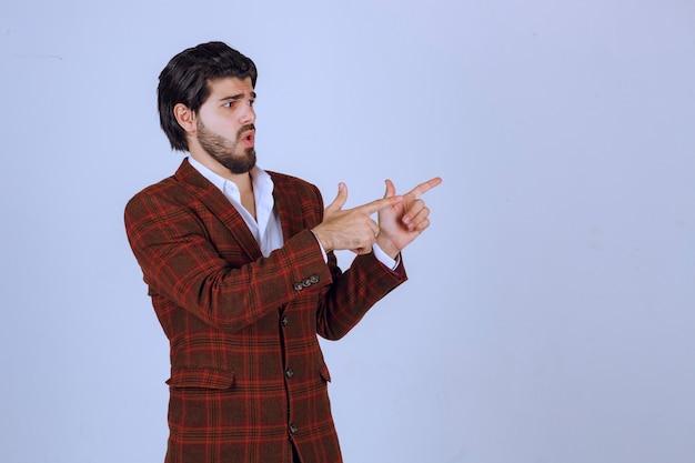 Homme en blazer à carreaux montrant quelque chose à droite et en parlant.