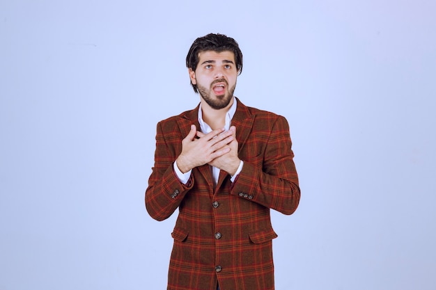 Homme en blazer à carreaux pointant et recevant des éloges pour lui-même.