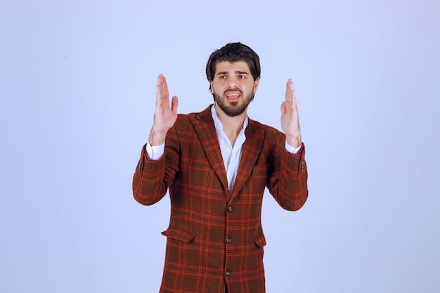Homme en blazer marron ayant un discours avec une large ouverture des mains.