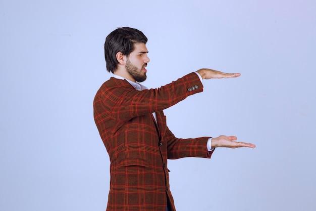 Homme en blazer marron montrant la hauteur d'un objet estimé.