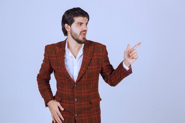 Homme en blazer marron pointant et introduisant quelque chose sur la droite.
