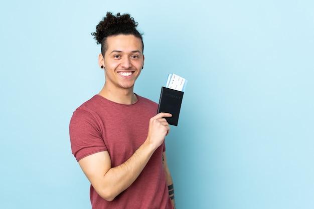 Homme sur bleu isolé heureux en vacances avec passeport et billets d'avion