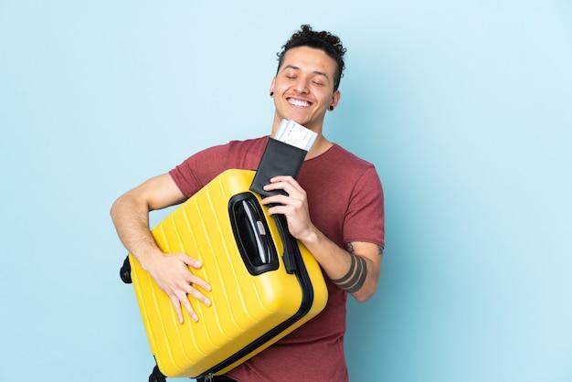 Homme sur bleu isolé en vacances avec valise et passeport