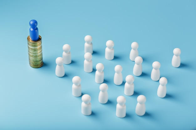 L'homme bleu se tient sur des pièces d'or en argent et contrôle une foule de blancs. le concept de pouvoir gourmand et de gestion des personnes.