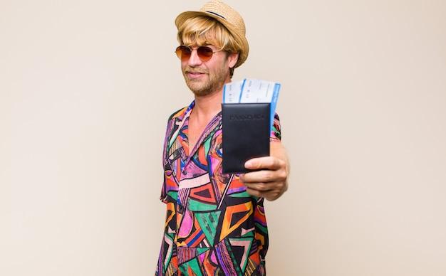 Homme blond adulte avec un passeport et des billets d'avion d'embarquement