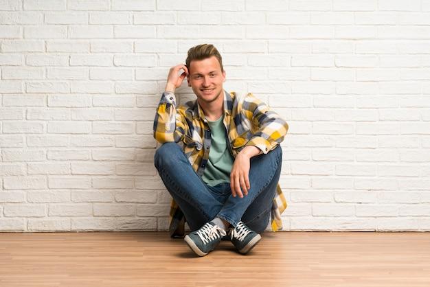 Homme blond assis sur le sol, pensant à une idée