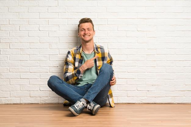 Homme blond assis sur le sol pointant sur le côté pour présenter un produit