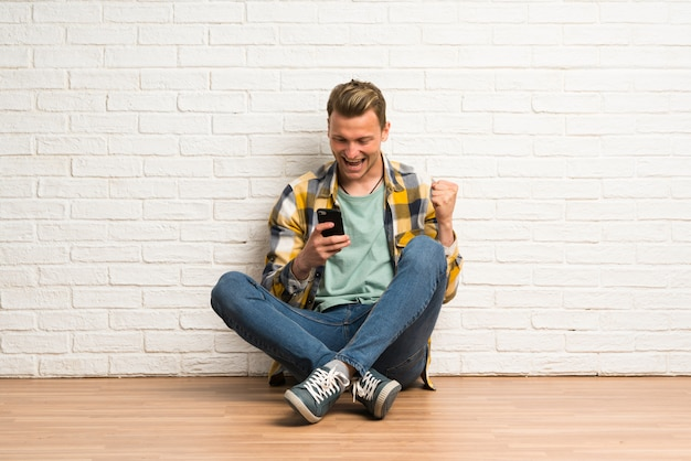 Homme blond assis sur le sol avec téléphone en position de victoire