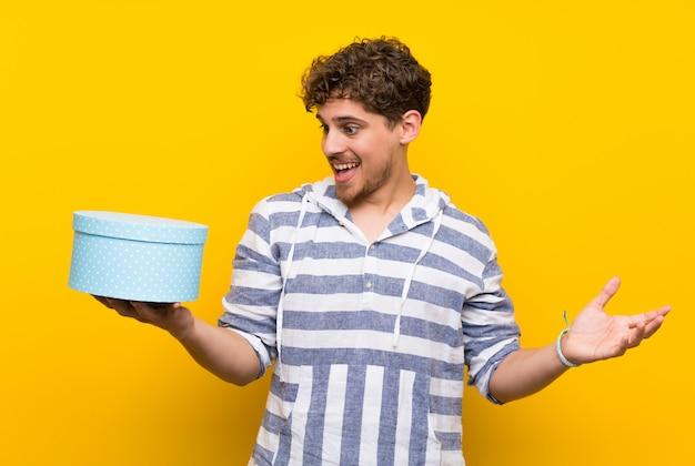 Homme blond au mur jaune tenant une boîte-cadeau dans les mains