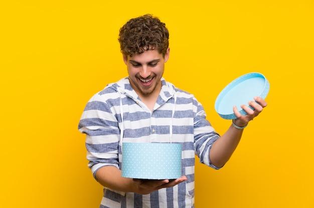 Homme blond au mur jaune tenant un cadeau dans les mains
