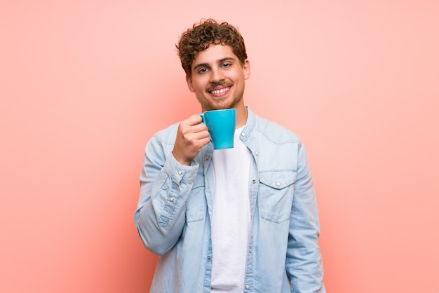 Homme blond au mur rose tenant une bonne tasse de café