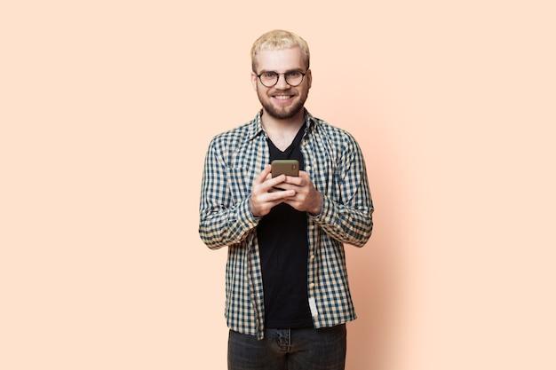 Homme blond avec barbe discute au téléphone et sourire en regardant la caméra à travers des lunettes sur le mur jaune du studio