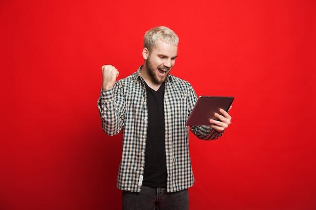 Homme blond avec barbe fait signe le signe gagnant tout en tenant sa tablette et posant sur un mur rouge