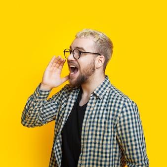 Homme blond avec barbe et lunettes crie