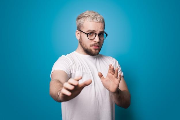 Homme blond avec barbe et lunettes fait des gestes de peur avec des paumes posant sur un mur de studio bleu