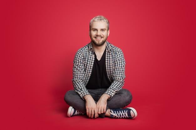 Homme blond et barbu assis sur le sol et sourit posant sur un mur rouge