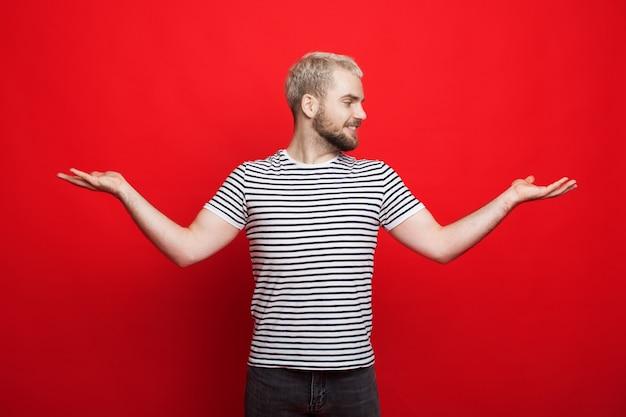 Homme blond caucasien avec barbe comparant deux choses dans ses paumes pose sur un mur rouge