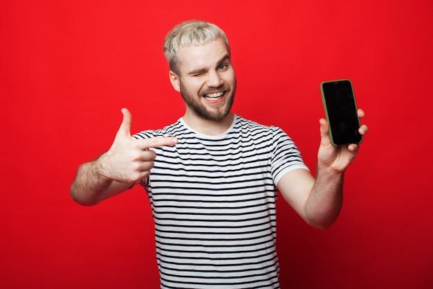 Homme blond caucasien avec barbe pointe vers son nouveau téléphone sur un mur de studio rouge