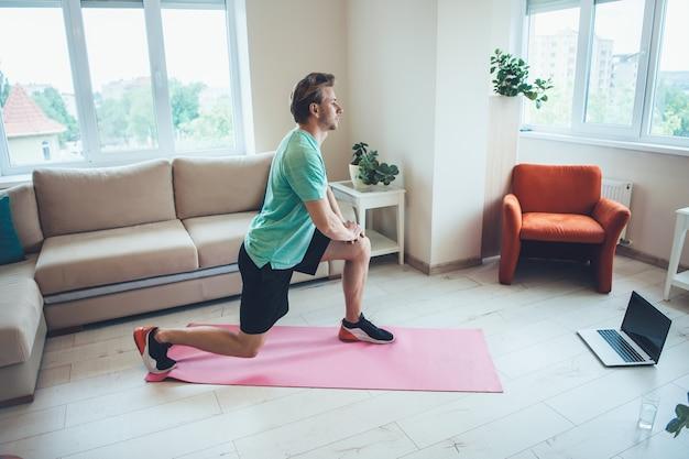 Homme blond caucasien en tenue de sport utilise un ordinateur portable à la maison tout en ayant des cours de fitness numérique
