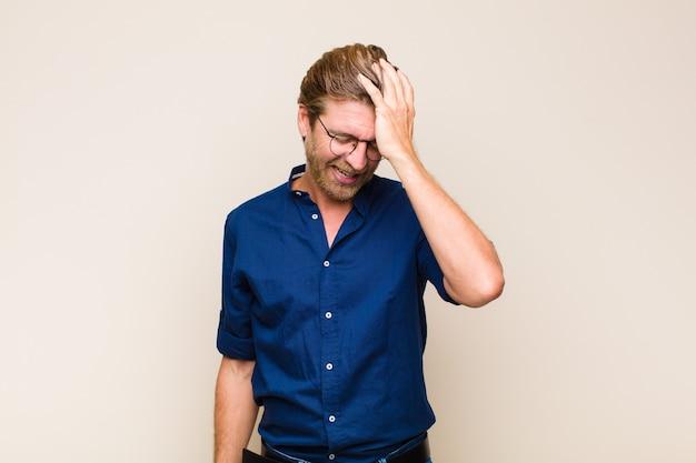 Homme blond caucasique adulte riant et frappant le front comme dire oh! j'ai oublié ou c'était une erreur stupide