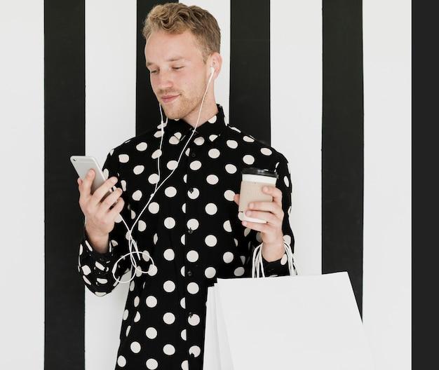 Homme blond en chemise tenant un café
