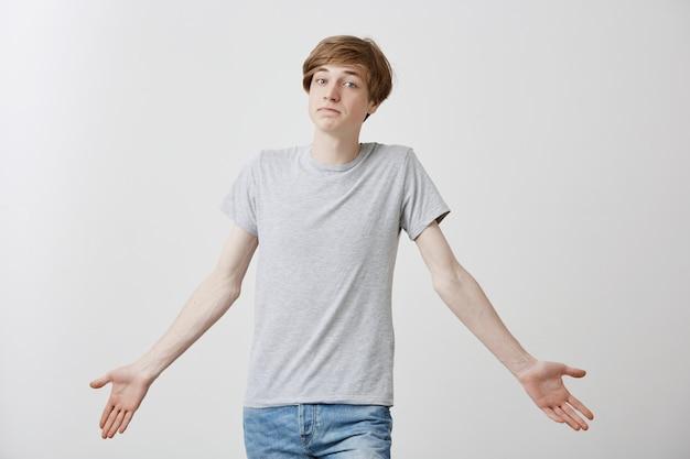 Homme blond clair aux yeux bleus, lèvres courbées, habillé avec désinvolture, debout haussant les épaules avec un air douteux ne sachant pas quoi choisir. concept de langage corporel
