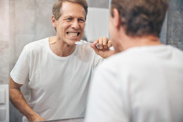 Homme blond concentré à la taille avec une brosse à dents debout dans une salle de bain