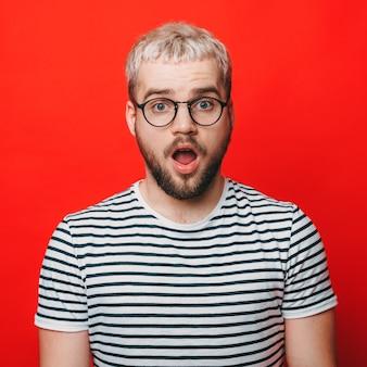 Homme blond gesticulant étonnement tout en portant des lunettes sur un mur de studio rouge