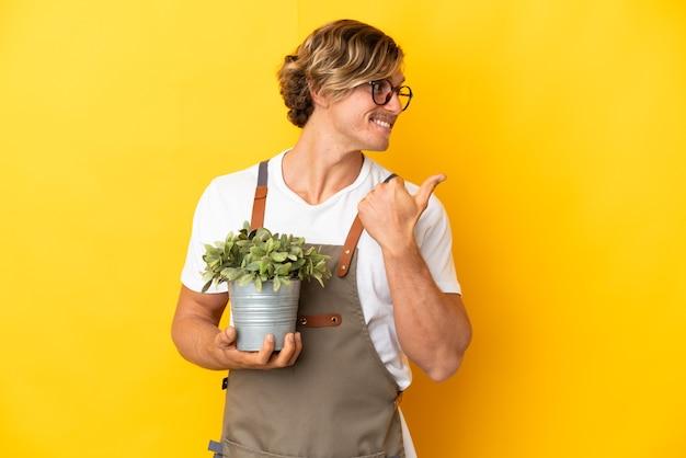 Homme blond jardinier tenant une plante isolée sur fond jaune pointant vers le côté pour présenter un produit