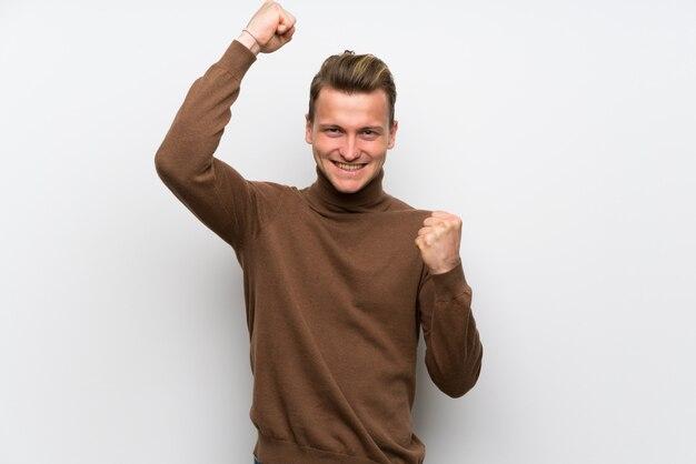 Homme blond sur un mur blanc isolé célébrant une victoire