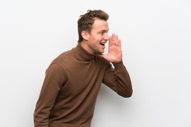 Homme blond sur un mur blanc isolé criant avec la bouche grande ouverte sur le côté