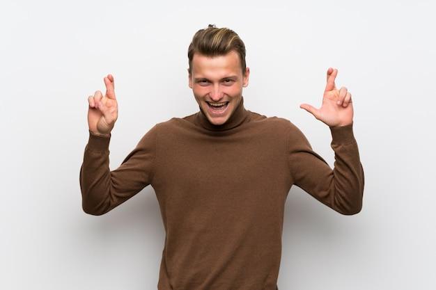 Homme blond sur un mur blanc isolé avec les doigts qui se croisent et souhaitant le meilleur