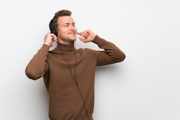Homme blond sur un mur blanc isolé, écouter de la musique avec des écouteurs