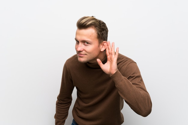 Homme blond sur un mur blanc isolé, écouter quelque chose en mettant la main sur l'oreille