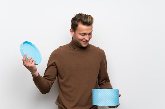 Homme blond sur mur blanc isolé, tenant un cadeau dans les mains