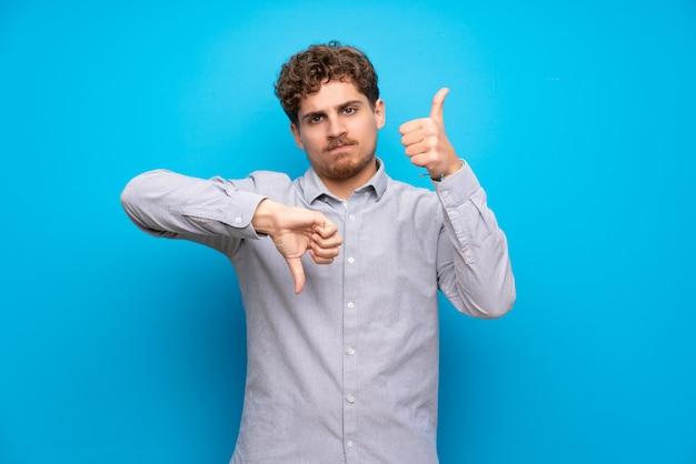 Homme blond sur un mur bleu faisant bon signe. indécis entre oui ou non