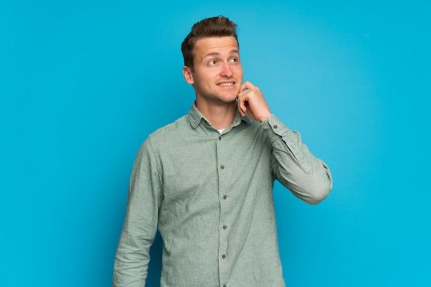 Homme blond sur un mur bleu isolé, pensant à une idée tout en levant