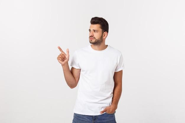 Homme blond sur mur jaune isolé effrayé et pointant vers le côté.