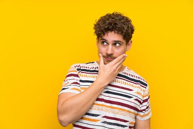 Homme blond sur un mur jaune pensant une idée