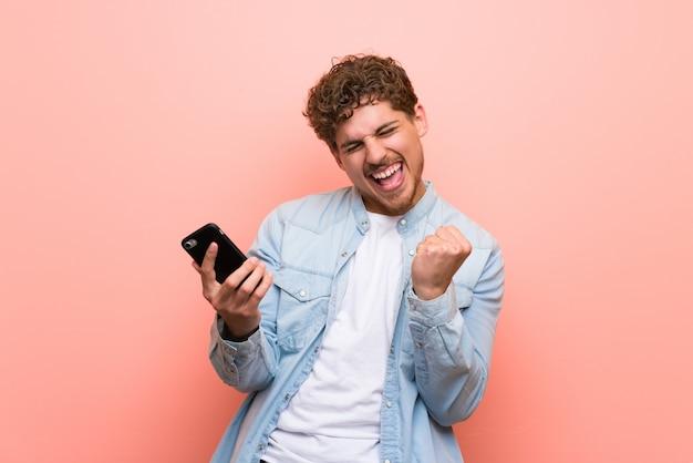 Homme blond sur un mur rose célébrant une victoire avec un téléphone portable