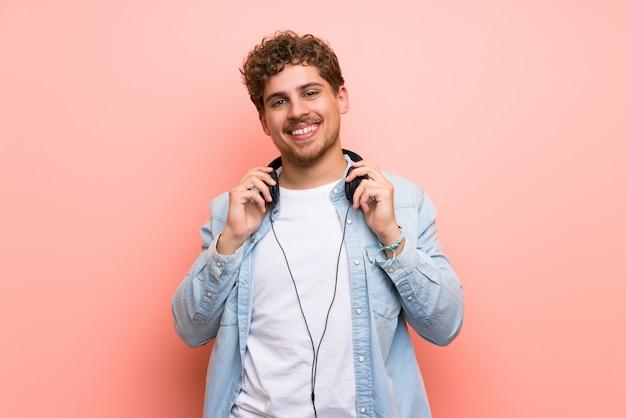 Homme blond sur un mur rose avec des écouteurs