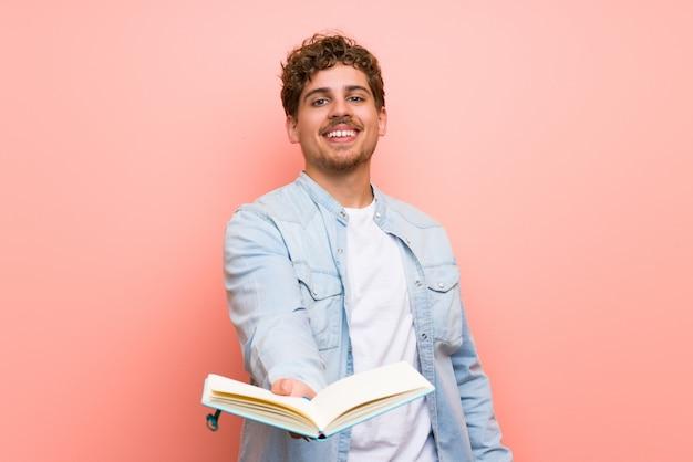 Homme blond sur un mur rose tenant un livre et le donnant à quelqu'un